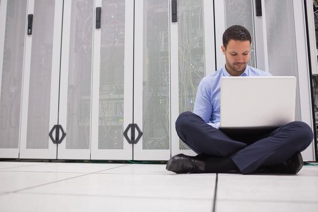 Technician sitting on floor working on laptop in data center.jpeg
