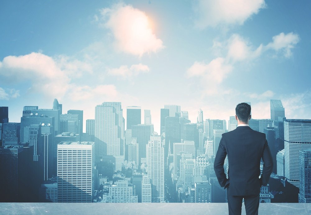 Businessman standing on a roof and looking at future city