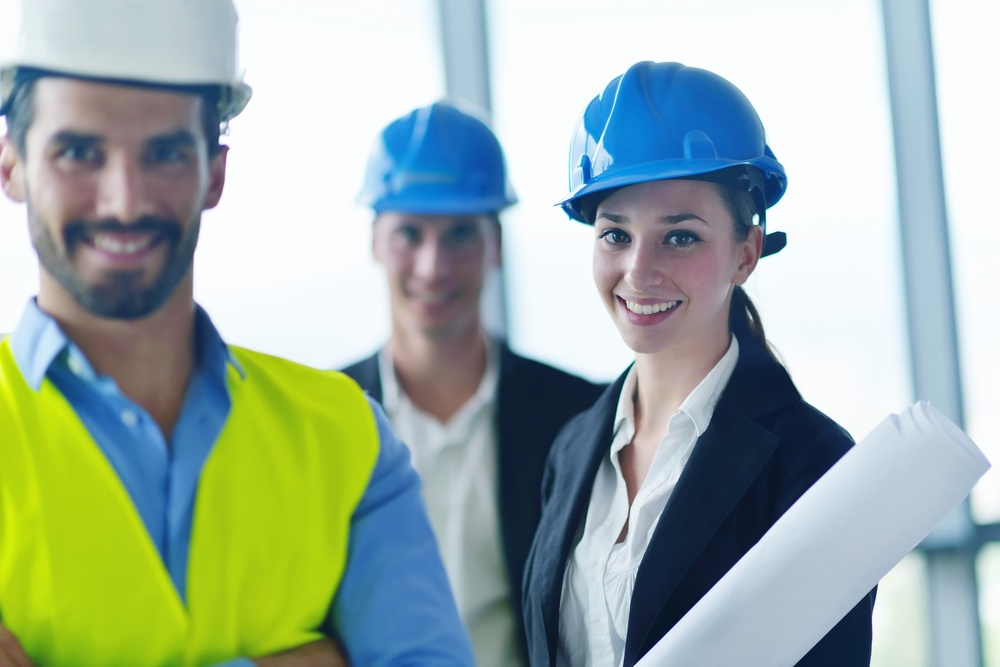 business people group on meeting and presentation  in bright modern office with construction engineer architect and worker looking building model and blueprint planbleprint plans.jpeg